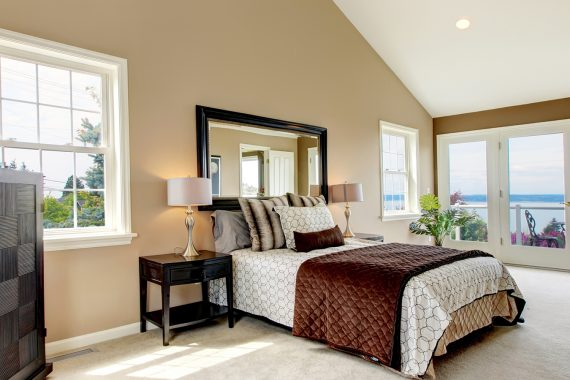 Classic luxury large bedroom with water view and carpet.